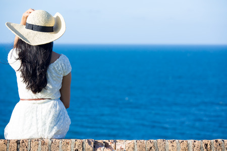 Closeup back view of woman sitting in white dress and hat looking out towards blue ocean and sky, isolated sea background photo
