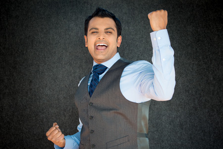 facial: Closeup portrait, handsome excited, energetic, happy, smiling student man winning, arms, fists pumped, celebrating success, isolated gray black background. Positive emotion, facial expressions
