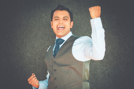 enrolled: Closeup portrait, handsome excited, energetic, happy, smiling student man winning, arms, fists pumped, celebrating success, isolated gray black background. Positive emotion, facial expressions.