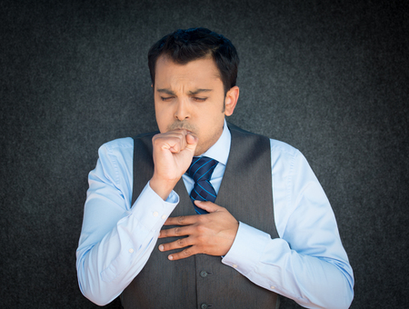 respiratory: Closeup portrait, sick mature worker, executive guy in blue tie and vest, having severe infectious cough, holding chest, raising fist to mouth looking miserable unwell, isolated gray black background.