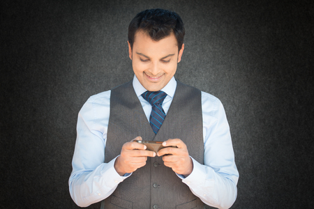 engrossed: Closeup portrait, young happy man in gray vest and blue tie looking down, engrossed, checking his cellphone, isolated black gray vignette background