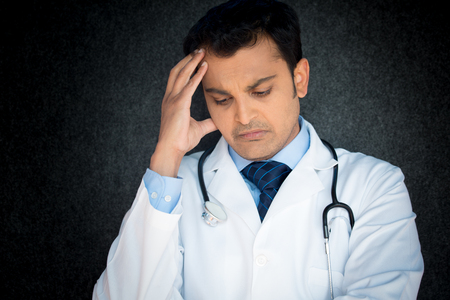 doctor stress: Closeup portrait, young depressed man healthcare practitioner holding face in despair, isolated black gray background