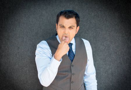 isolated on gray: Closeup portrait of young angry, unhappy, business man, student, employee, finger in mouth, something sucks, gag, isolated gray background. Negative facial emotions, expressions, feelings