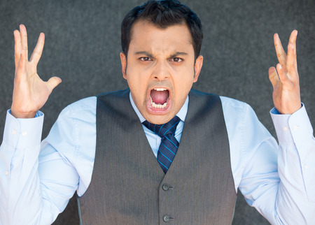 angry person: Closeup portrait of bitter displeased pissed off, angry grumpy man in tie, open mouth, hands in air, screaming and yelling, isolated gray background. Negative human emotion facial expression feeling