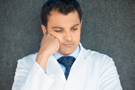 Closeup portrait, young depressed man healthcare practitioner holding face in despair, isolated gray background 免版税图像 - 37378714