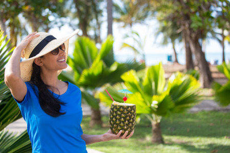 pineapple tree: Closeup portrait, woman in blue shirt and brown straw hat holding pineapple mixed drink with rum at resort, isolated background of green palm trees