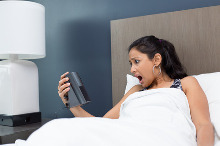 indian girl: Closeup portrait, young woman in bed, wide open mouth, shocked by alarm clock, what time it is, late for work. isolated indoors room background