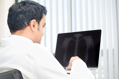Closeup portrait of intellectual man healthcare personnel with white labcoat, looking at chest x-ray radiographic image, on laptop isolated hospital clinic background. Radiology department
