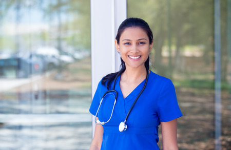 hospital: Closeup portrait of friendly, smiling confident female doctor, healthcare professional in blue scrubs with stethoscope, standing outside hospital background