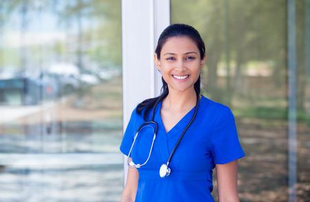 Primer retrato de amable, sonriente mujer médico confianza, profesional de la salud en batas de color azul con estetoscopio, permanente de fondo fuera del hospital Foto de archivo - 37790396