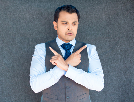 Closeup portrait of young business man thinking, daydreaming,pointing opposite directions, looking confused, isolated gray background. Negative emotion facial expression. Short-term memory loss