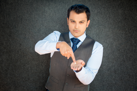 Closeup portrait of mean young man in vest and tie pointing at palm hand, indicating that it is pay day, time to pay up, isolated black gray background Imagens
