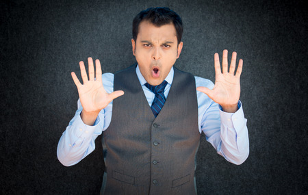Closeup portrait of young, angry man in vest and blue tie, gesturing no with hands and saying stop with his mouth, isolated on gray black background