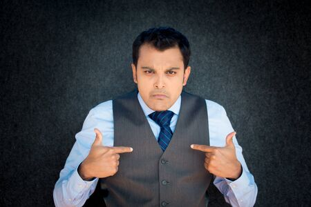 arrogant: Closeup portrait, young gentleman in vest and blue tie, clutching chest tightly in severe substernal pain, grimace face, isolated gray black background