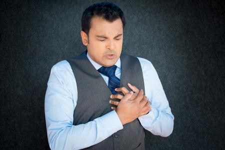 ポートレート、クローズ アップ、若い紳士はベストと青いネクタイ、胸骨痛でしっかりと握りしめ胸で顔をしかめる顔、孤立した灰色の黒の背景 写真素材
