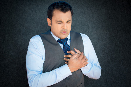 attacks: Closeup portrait, young gentleman in vest and blue tie, clutching chest tightly in severe substernal pain, grimace face, isolated gray black background