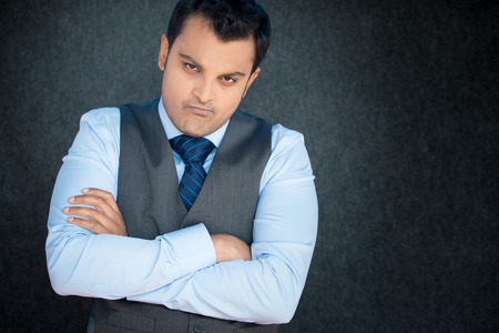 Closeup portrait, displeased, angry, grumpy business man, bad attitude, arms crossed, folded, looking at you, isolated gray black background. Negative human emotion, facial expression, feeling Stock Photo