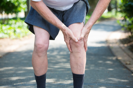 artrosis: Primer cosechado retrato, hombre mayor con la camisa blanca, pantalón gris, de pie en la carretera pavimentada, en el dolor de rodilla grave, árboles aislados fuera al aire libre de fondo.