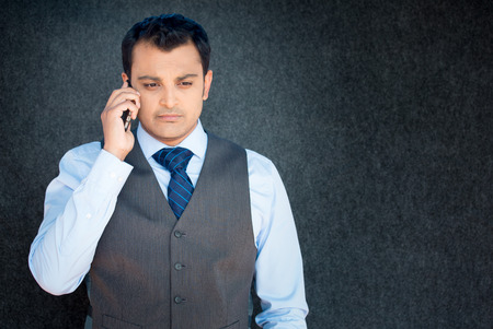 isolated on gray: Closeup portrait, unhappy worried young man in vest and tie talking on phone, isolated gray black background. Negative human emotions, facial expressions, feelings, reaction. Bad news. Stock Photo