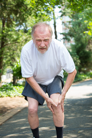 senior pain: Closeup portrait, older man in white shirt, gray shorts, standing on paved road, in severe knee pain, isolated trees outside outdoors background. Stock Photo