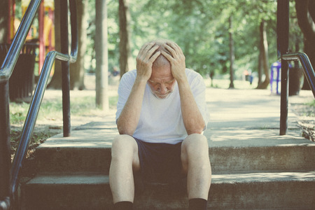 citizens: Closeup portrait, senior mature man in black shorts and white shirt, sitting down outside on steps, hands on head in defeat, depression, failure. Retro faded vintage look