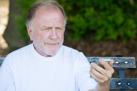 skeptical: Closeup portrait of funny elderly man in white shirt, skeptical, checking smartphone, sending text message, seated on a bench, isolated outdoor background. Stock Photo