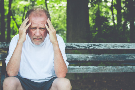 body expression: Closeup portrait, stressed older man in white shirt, hands on head with bad headache, sitting on bench, isolated background of trees outside.