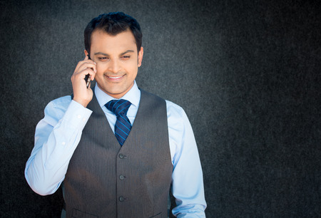 pleasant emotions: Closeup portrait, handsome young business man, happy guy, in vest and tie, using cell phone, smiling, having pleasant conversation, isolated gray black background. Human emotions, expression