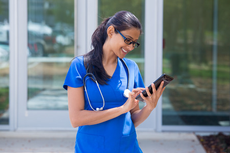 Closeup portrait of friendly, smiling confident female doctor in black glasses,  blue scrubs with stethoscope, analyzing patient data on black digital tablet, outside hospital background