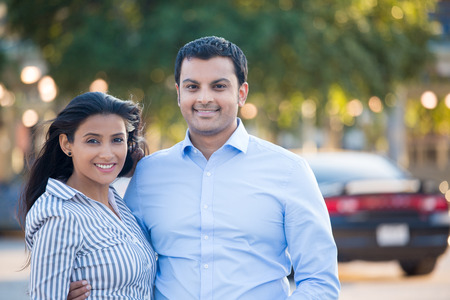 Closeup portrait, attractive wealthy successful couple in blue shirt and striped outfit holding each other smiling, isolated outside green trees and black car background.