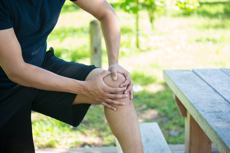 Closeup cropped portrait, man in black shirt and shorts holding knee in severe pain, isolated trees and picnic bench outside background. Stockfoto