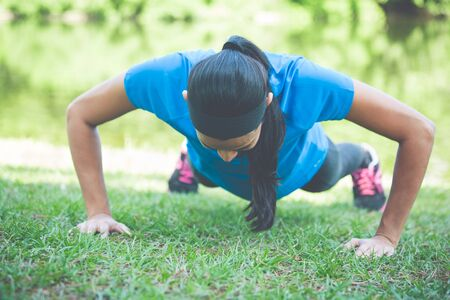 pushup: Closeup portrait, young healthy woman in blue shirt performing pushup outside on grass in park, isolated trees and water background. Stock Photo