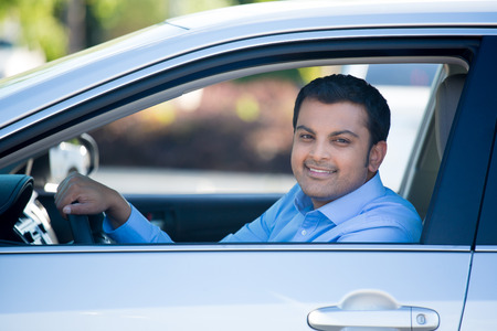 Closeup portrait, young handsome man in his new silver gray car, relaxing, hand on steering wheel, looking out window, isolated on outdoors background with vehicle.