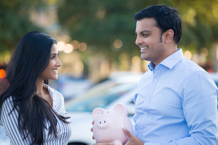 indian business man: Closeup portrait, smiling happy man in blue shirt and woman holding piggy bank, isolated outdoors background with car and trees. Smart financial investments and advice