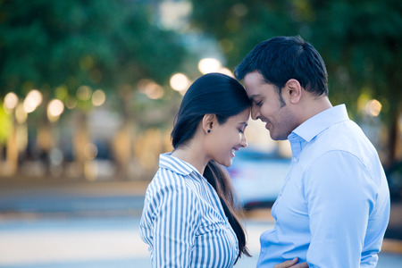 hispanic girls: Closeup portrait, young couple in blue shirt, head to head, eyes closed in love smitten, isolated outdoors outside background. Happy moments, positive emotions