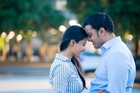 Retrato do close up, o jovem casal na camisa azul, cabeça a cabeça, os olhos fechados no amor ferido, isolado outdoors fundo fora. Momentos felizes, emoções positivas