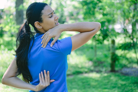 ache: Closeup portrait, young woman in pigtail and blue shirt feeling severe tormenting agony from back neck pain, isolated green trees background outside outdoors Stock Photo
