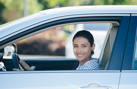 Closeup portrait, young pretty happy woman in her new silver gray car, relaxing, hand on steering wheel, looking out window, isolated on outdoors background with vehicle. Stock Photo