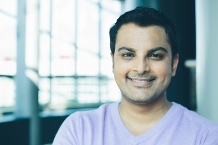 pozitivní: Detailním headshot portrét, šťastný hezký obchod muž, s úsměvem, v fialové svetru, sebevědomý a přátelský na izolované kancelářském interiéru pozadí. Firemní úspěch