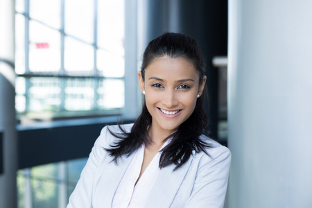 Closeup portrait, young professional, beautiful confident woman in gray white suit, friendly personality, smiling isolated indoors office background. Positive human emotions Foto de archivo