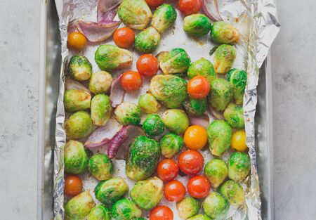 pans: Closeup portrait of oven baked and spiced vegetables in pan lined by aluminum foil, isolated gray white marble background. Creative cooking. High vitamin c and minerals Stock Photo