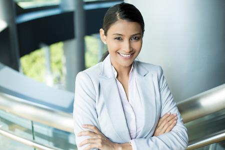 Großansicht Porträt, junge professionelle, schöne zuversichtlich Frau in rosa T-Shirt grauer Anzug, die Arme verschränkt gefaltet, lächelnd in Innenräumen Bürohintergrund. Positive menschlichen Emotionen Standard-Bild