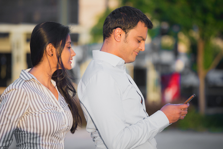 Closeup portrait, woman watching man over shoulder happily texting someone else, isolated outdoors background. Negative emotion facial expression feelings conflict concept