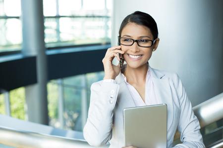 fille indienne: Portrait Gros plan, attrayant femme heureuse en costume blanc gris et lunettes noires utilisant pc d'argent et le téléphone, isolé interior fond de bureau. Émotion humaine positive expressions faciales des sentiments