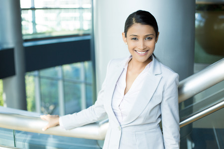 Closeup portrait, young professional, beautiful confident woman in gray white suit, friendly personality, holding rail, smiling isolated indoors office background. Positive human emotions