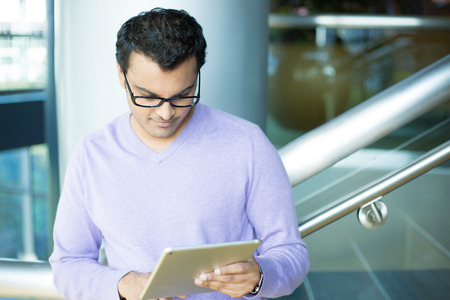 indian business man: Closeup portrait, young captivated, absorbed, engrossed man in purple sweater and black eye glasses perusing, pondering emails on silver gray tablet touch-pad, isolated indoors background