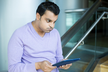 puffed cheeks: Closeup portrait, very upset, fuming, incensed man in purple sweater reading something negative news on silver gray tablet, funny facial expression puffed out cheeks, isolated indoors background