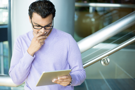 interested: Closeup portrait, young captivated, absorbed, engrossed man in purple sweater and black eye glasses perusing, pondering emails on silver gray tablet touch-pad, isolated indoors background