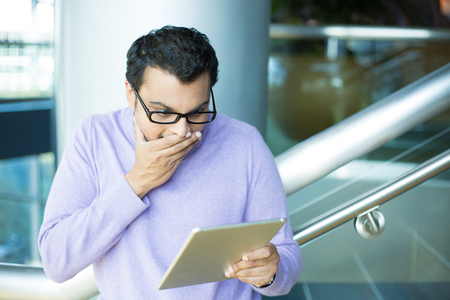chuckle: Closeup portrait, young happy man in black eyeglasses and purple sweater, astonished, hand on mouth concealed laugh, by what he sees on tablet, isolated indoors office background