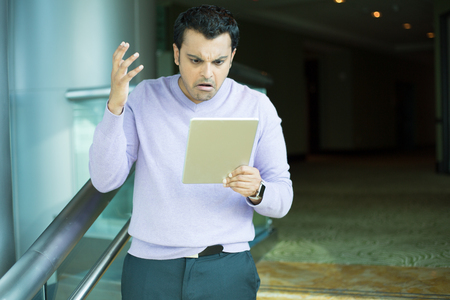 incensed: Closeup portrait, very upset, fuming, incensed man in purple sweater reading something negative news on silver gray tablet, isolated indoors background Stock Photo